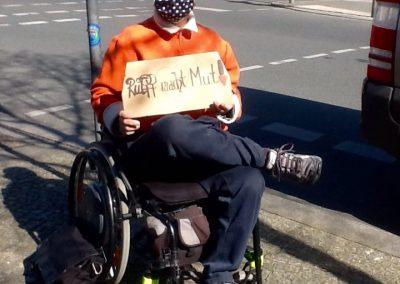 Das Bild zeigt eine Frau im Rollstuhl mit einer Atemschutzmaske