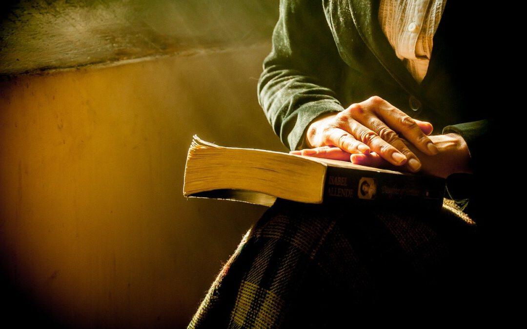 Das Bild zeigt eine alte Frau mit einem Buch auf dem Schoß