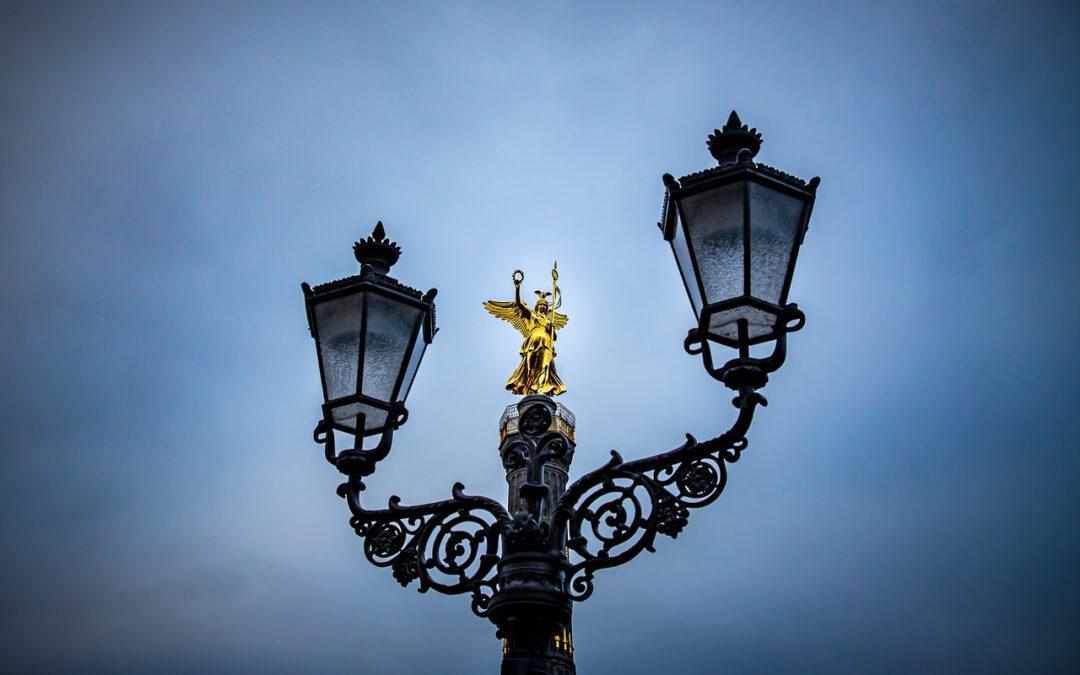 Das Bild zeigt eine antike Straßenlaterne mit einer verkleinerten Berliner Siegessäule