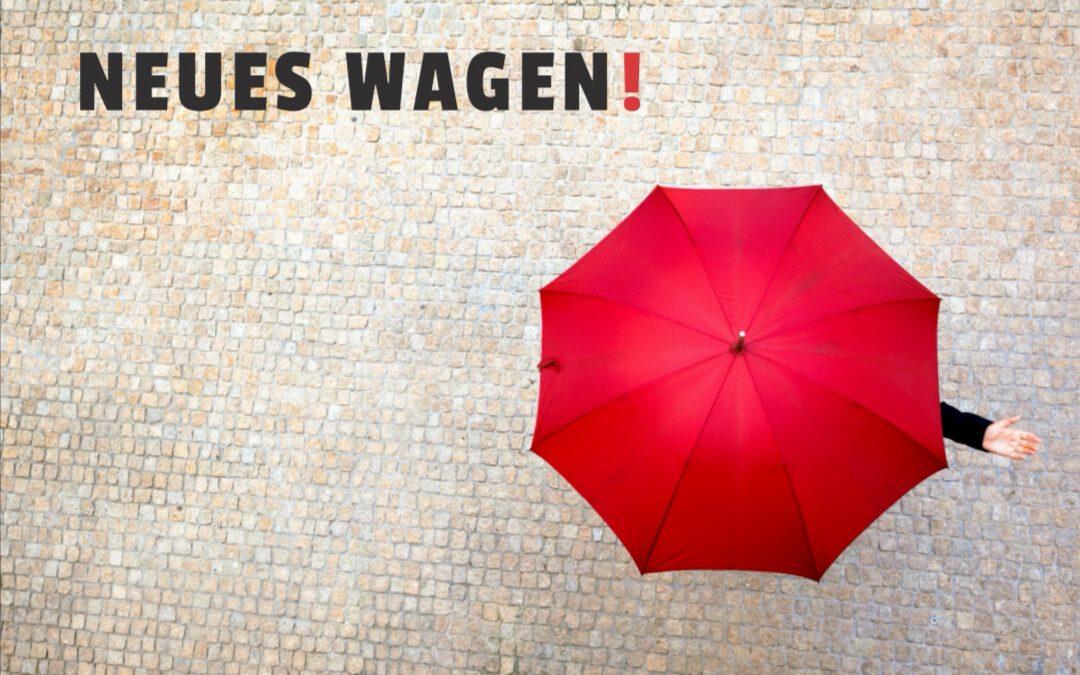 Das Bild zeigt einen roten Regenschirm mit der Überschrift Neues wagen!