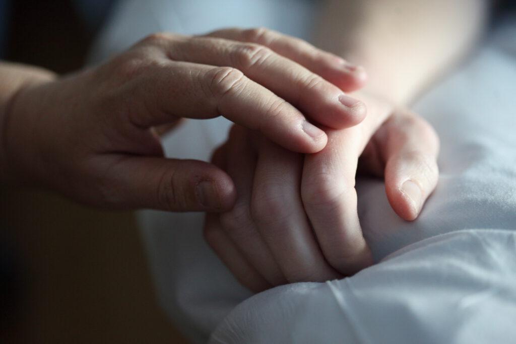 Das Foto zeigt zwei aufeinanderliegende Hände